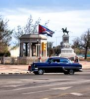 Blue Ford drives by the Cuban Flag