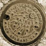 """New Orleans Water Meter Cover (Sepia)"" by NOLAlphabet"