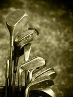 Old set of rough used golf clubs sepia image