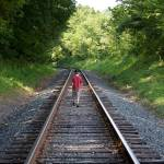 """Boy walking on train tracks"" by vphowe"