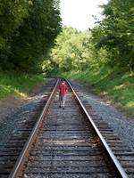 Boy walking on train tracks