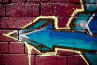 Graffiti arrow on the textured brick wall