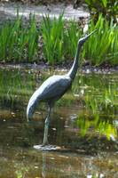wading bird statue in woodland garden