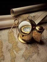 An old fashioned binicle compass with a map.