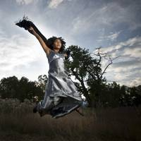 a young woman, in a silver dress, leaps into the a