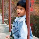 """Asian child sitting on a bridge"" by BehindTheLens"