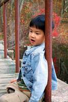 Asian child sitting on a bridge