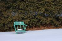 A green chair stands forgotten in snow