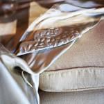 """silk sheet on sofa cushion through shop window"" by nathangriffith"