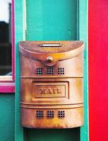 copper mailbox hanging on colorful awning