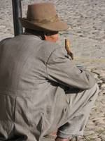 Old Peruvien man wearing a hat resting