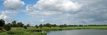 Dutch countryside with dike under summer clouds.