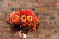 A colorful red and orange bridal bouquet of flower
