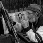 """Artist painting through a magnifying glass"" by AManWithACamera"