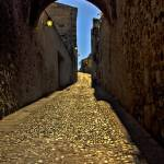 """Old arch over narrow street in Caceres"" by kingafoto"