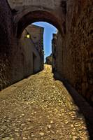 Old arch over narrow street in Caceres