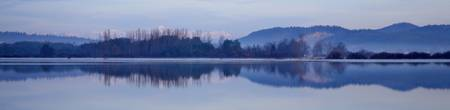 Cerknica lake at dawn with snow covered alps
