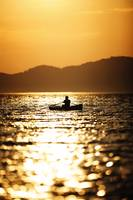 Sunset silhouette of a rower on water photograph