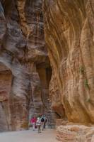 Tourists walk through towering canyon leading to P