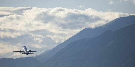 Airplane taking off over the alpine mountains