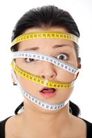 Woman with measuring tape around her head.