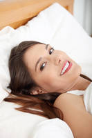 Portrait of beautiful smiling woman on bed.