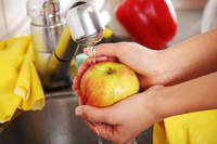 Woman hands washing apple.