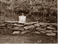old moonshine jug on rock wall