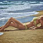 """Young blond woman sun tanning lazing at the beach."" by amynnasser"