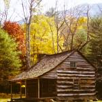 """Log Cabin in Fall Trees"" by darknesstolight"