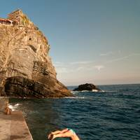 Vernazza, a man jump in the clear water