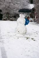 Boy Peeking from Behind Snowman