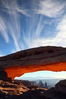 Mesa arch glowing red at sunrise in Canyonlands Na