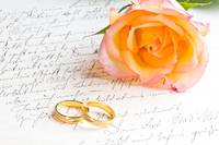 Rose and two rings over handwritten love letter