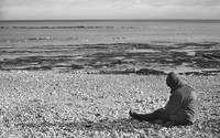 Lone Man Sitting on Pebble Beach