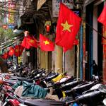 """Motorcycles and flags in Hanoi, Vietnam"" by veitschuetz"