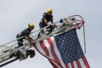 Firefighters Hanging USA Flag From Ladder