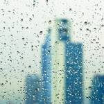 """Raindrops on window with building in background"" by ingojez"