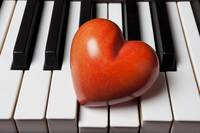 Red stone heart on piano keys