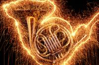 French horn outlined with sparks