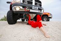 Sexy woman repairing the red jeep