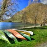 """Kayaks on shore of Glendhu Bay"" by tanalised"