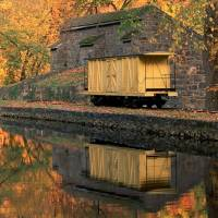 Yellow Traincar and Fall Foliage Next to a River Art Prints & Posters by Eugene Kolchak