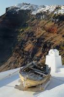 Santorini's old boat with Imerovigli's village in