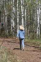 Young Blond Girl Walking Down a Forest Path