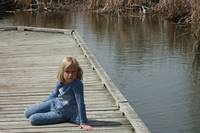 Young Blond Girl sitting on a dock