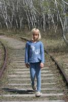 Young Blond Girl walking along railway