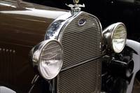 Detail of the headlights and radiator of a old car