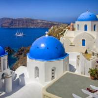 Santorini Images - The Blue Domes and a Sailboat Art Prints & Posters by Rob Greebon