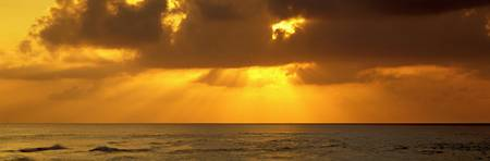 Sunbeams radiating through clouds over the ocean